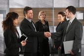 pic of business meetings  - Happy businesspeople shaking hands greeting each other before business meeting in office - JPG