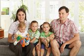 image of nuclear family  - Portrait of happy nuclear family with 3 children sitting on sofa at home - JPG