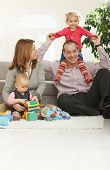 image of nuclear family  - Happy family of four sitting at home on floor of living room - JPG
