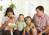 picture of nuclear family  - Portrait of nuclear family with 3 children sitting on sofa at home - JPG