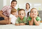 Happy family with 3 children sitting on floor of living room at home.?
