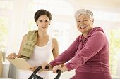 stock photo of personal trainer  - Healthy elderly woman training at home with exercise bike - JPG