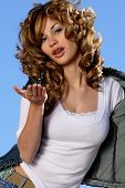 stock photo of brown-haired  - Young beautiful Spanish girl blowing a kiss - JPG