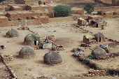stock photo of mud-hut  - Traditional straw huts and mud houses in Hombori in Mali - JPG