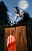 stock photo of werewolf hunter  - Scary man sitting on a doghouse and turning into werewolf - JPG