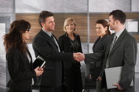 stock photo of business meetings  - Happy businesspeople shaking hands greeting each other before business meeting in office - JPG
