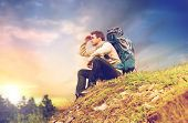 travel, tourism and hike concept - male traveler with backpack sitting on ground and looking far awa poster