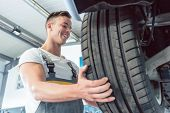 Low-angle view of the hand of a skilled auto mechanic holding a new high-quality tire during work in poster