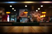 Empty Wooden Table Top With Blur Coffee Shop Or Restaurant Interior Background. poster