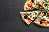 Sliced Hot Pizza With Seafood, Cheese And Herbs  On Black Background For Lunch Or Dinner Crust. Pizz poster
