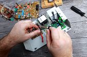 The Master On Repair Of The Radio Electronic Equipment Removed The Payment Scheme From The Electroni poster