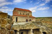 Ancient Church In Ancient Cave Town. Georgia. Sunny Summer Day With Light Clouds. poster