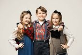 Cute Stylish Children On White Studio Background. Two Beautiful Teen Girls And Boy Standing Together poster