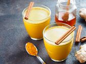 Healthy Drink Golden Turmeric Latte In Glass.gold Milk With Turmeric, Ginger Root, Cinnamon Sticks,  poster