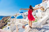 Europe travel vacation fun summer woman dancing in freedom with arms up happy in Oia, Santorini, Gre poster