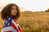 Sad depressed mixed race African American girl teenager female young woman in a field of wheat or ba poster