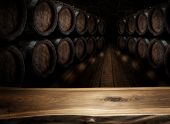 Old wooden table top and oak wine barrels at the background. Wine background. poster
