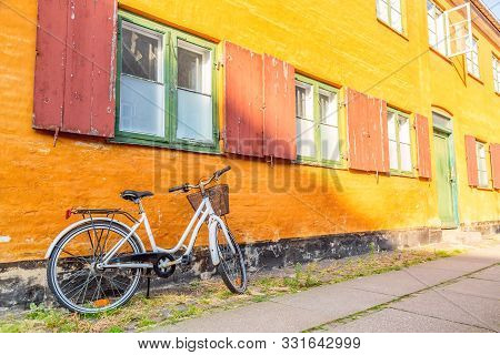 poster of Picturesque Of Copenhagen. Old Yellow House Of Nyboder District With Bike. Old Medieval District In