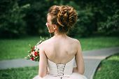 Summer Wedding Photo: A Young Slim Brown-haired Bride Bride Stands With Her Back With An Open Back I poster
