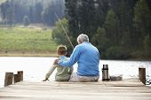 stock photo of grandfather  - Senior man fishing with grandson - JPG
