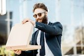 Portrait Of A Bearded Businessman Dressed In The Suit Feeling Hungry While Opening Pizza Box Outdoor poster