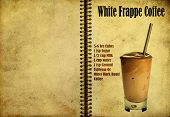 stock photo of frappe  - Oldvintage or grunge Spiral Recipe Notebook with White Frappe Coffee cocktail on the page - JPG