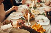 Closeup Of People Sitting At Dining Table On Christmas And Joining Hands In Prayer, Copy Space poster