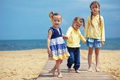 image of children playing  - Group of kids playing at the beach - JPG