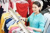 stock photo of blouse  - Young woman choosing shirt and blouse during clothing shopping at store - JPG