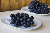 Bunches Of Fresh Ripe Red Grapes On A White Plate On A Wooden Light Background. Grapes Background. S poster