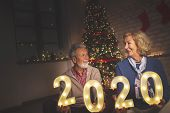 Senior Couple Sitting In Front Of Nicely Decorated Christmas Tree, Holding Illuminating Numbers 2020 poster