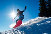 Snowboarder Riding Red Snowboard in the Mountains at Sunny Day. Snowboarding and Winter Sports poster