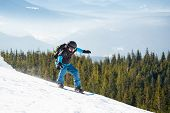 Snowboarder Riding Snowboard in the Mountains at Sunny Day. Snowboarding and Winter Sports poster