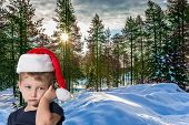 Handsome little boy in red Santa Claus hat is sad. The snow-covered coniferous forest. Lapland. The  poster
