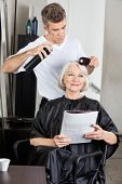 stock photo of hairspray  - Senior woman with magazine getting her hair done by male hairdresser in salon - JPG