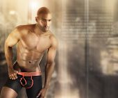 Sexy muscular male model in underwear against modern futuristic abstract background with lots of cop