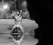 Classic black and white scenic portrait of beautiful muscle man at rocky beach