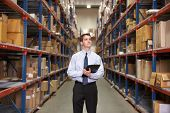stock photo of warehouse  - Manager In Warehouse With Clipboard - JPG