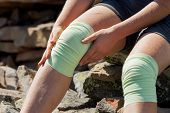 foto of knee-cap  - Athlet looking girl fixes bandage on knees outdoor - JPG