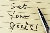image of goal setting  - Set your goals words written on lined paper with a pen on it - JPG