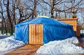 foto of yurt  - One blue yurt with big closed decorated orange door in the winter park - JPG