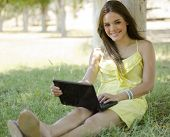 stock photo of telecommuting  - Cute young woman telecommuting and relaxing at a park - JPG