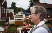 picture of junk-yard  - An old woman at a yard sale - JPG