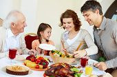 stock photo of happy thanksgiving  - Portrait of happy family sitting at festive table while having Thanksgiving dinner - JPG