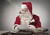 image of letters to santa claus  - Santa Claus smoking a pipe and reads gifts requests - JPG