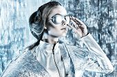 Beautiful young woman in silver latex costume and glasses with futuristic hairstyle and make-up. Sci