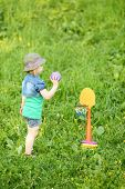 image of bolero  - Little pretty girl plays mini basketball at green meadow at sunny day - JPG