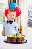 foto of cake stand  - Portrait of happy boy standing in front of birthday cake at home - JPG