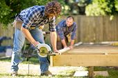 stock photo of cut  - Mid adult carpenter cutting wood with handheld saw while coworker helping him in background at construction site - JPG