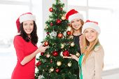 christmas, x-mas, winter, happiness concept - three smiling women in santa helper hats decorating a